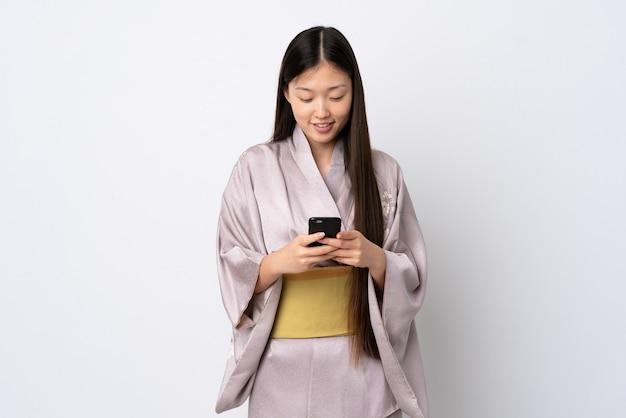 携帯電話でメッセージを送信する着物を着ている若い中国人の女の子