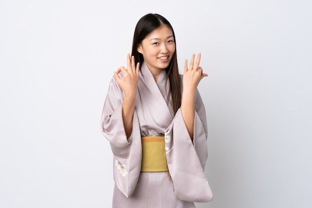 Young chinese girl wearing kimono showing ok sign with two hands