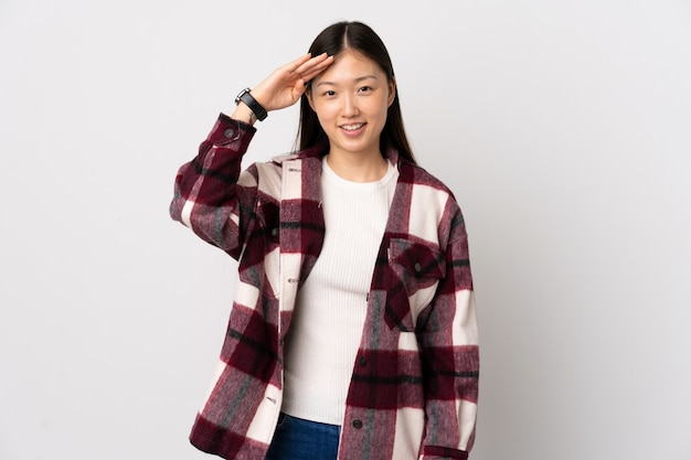 Young chinese girl over white wall saluting with hand with happy expression