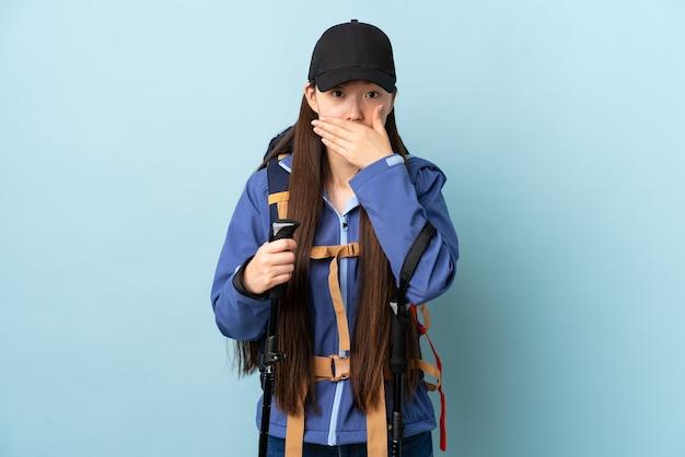 배낭과 손으로 입을 덮고 파란색 위에 트레킹 기둥을 가진 젊은 중국 소녀