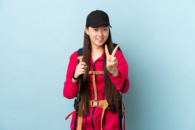 バックパックと青い笑顔と勝利の兆候を示すトレッキングポールを持つ若い中国の女の子