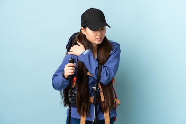 Молодая китаянка с рюкзаком и треккинговыми палками над синей стеной, страдающая от боли в плече за усилие