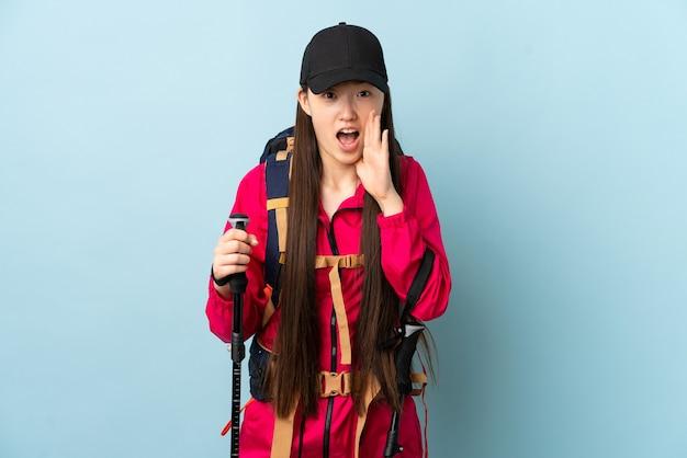 孤立した青い背景の上にバックパックとトレッキングポールを持つ若い中国の女の子が叫び、何かを発表します