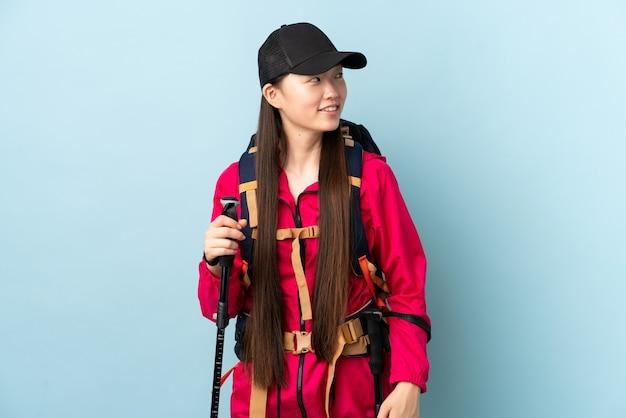 見上げながらアイデアを考えて孤立した青の上にバックパックとトレッキングポールを持つ若い中国の女の子