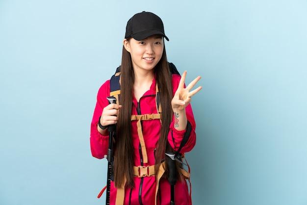 Молодая китаянка с рюкзаком и треккинговыми палками над изолированной синей стеной счастлива и считает три пальцами