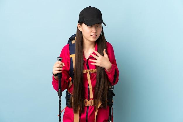 心臓の痛みを持っている孤立した青い壁の上のバックパックとトレッキングポールを持つ若い中国の女の子