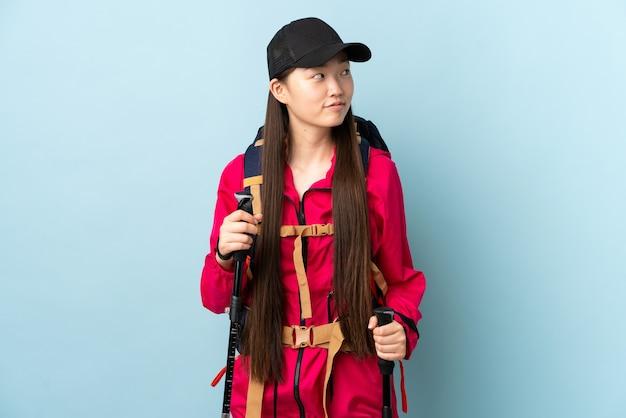 배낭과 측면을 찾고있는 동안 의심을 갖는 고립 된 파란색 벽 위에 트레킹 기둥을 가진 젊은 중국 소녀