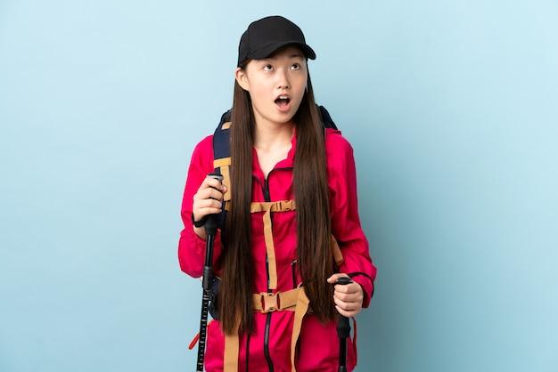 배낭과 고립 된 파란색 벽을 통해 트레킹 기둥을 찾고 놀란 표정으로 젊은 중국 소녀