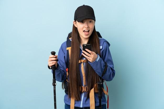 孤立した青い壁にバックパックとトレッキングポールを持つ若い中国の女の子は驚いてメッセージを送信します