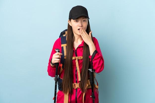 Молодая китаянка с рюкзаком и треккинговыми палками над изолированной синей стеной, зевая и прикрывая широко открытый рот рукой