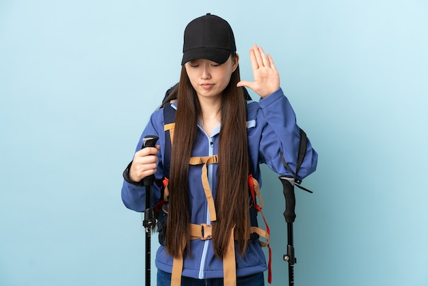 Young chinese girl with backpack and trekking poles on isolated blue making stop gesture and disappointed