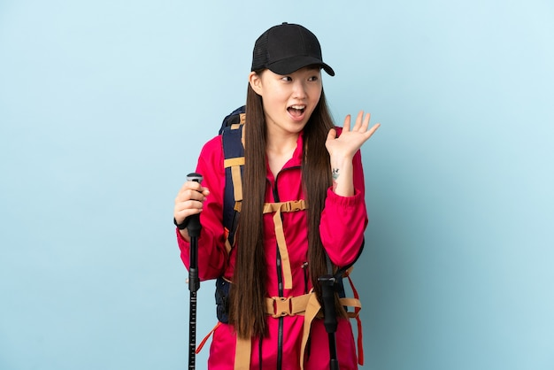 Young chinese girl with backpack and trekking poles isolated