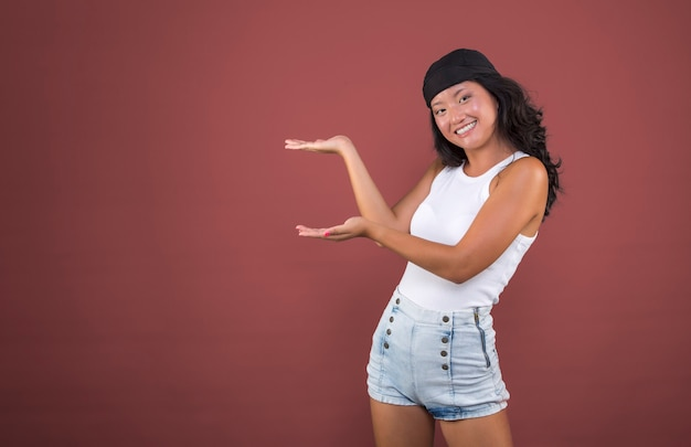 Young chinese girl with bandana and isolated t-shirt pointing to the side showing something.