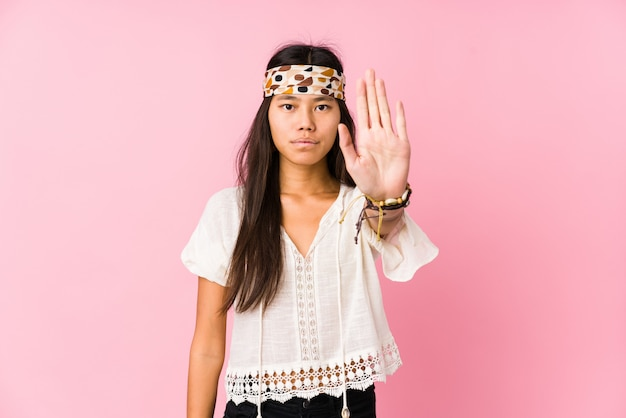 Young chinese hippie isolated standing with outstretched hand showing stop sign, preventing you.