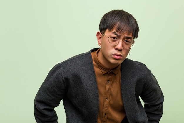 Young chinese man against a green wall