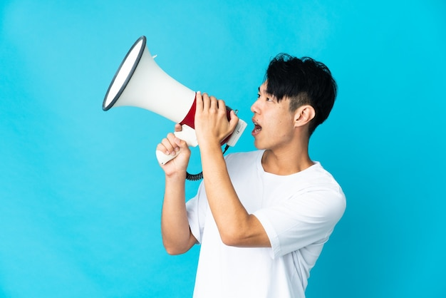 Young chinese man on blue shouting through a megaphone to announce something in lateral position