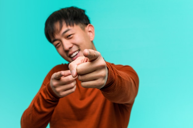 Young chinese man cheerful and smiling pointing to front