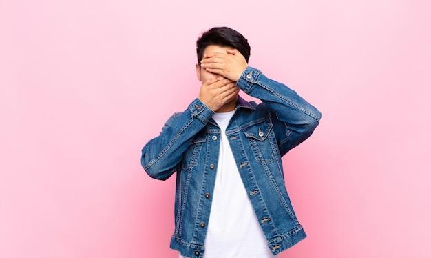 Молодой китаец сжимает лицо обеими руками, говоря «нет»! отказ от картинок или запрет фото на плоской цветной стене