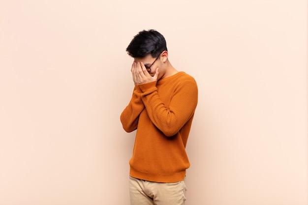 Молодой китаец закрывает глаза руками с грустным, разочарованным взглядом отчаяния, плача, вид сбоку на ровную цветную стену