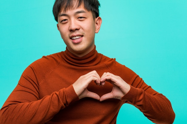 Young chinese man doing a heart shape with hands