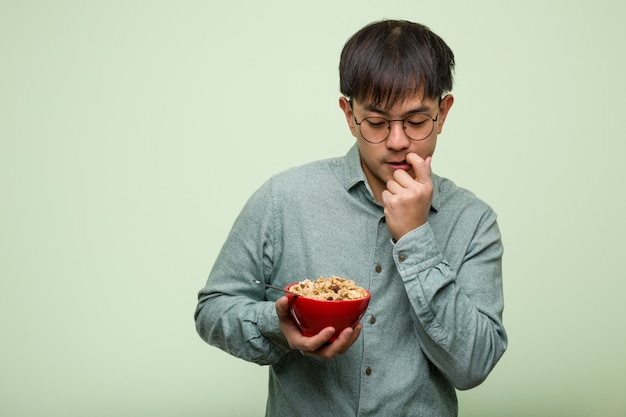Young chinese man eating a cereals bowl