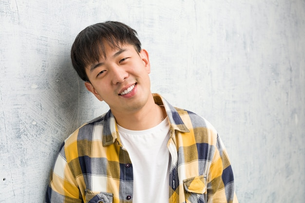 Young chinese man face closeup cheerful with a big smile