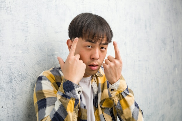 Young chinese man face closeup doing a concentration gesture