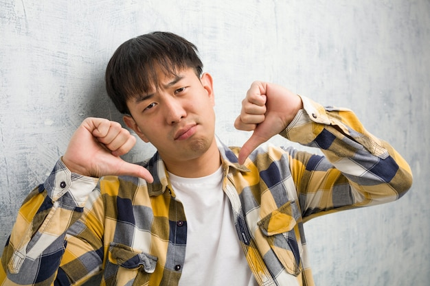 Young chinese man face closeup pointing fingers, example to follow