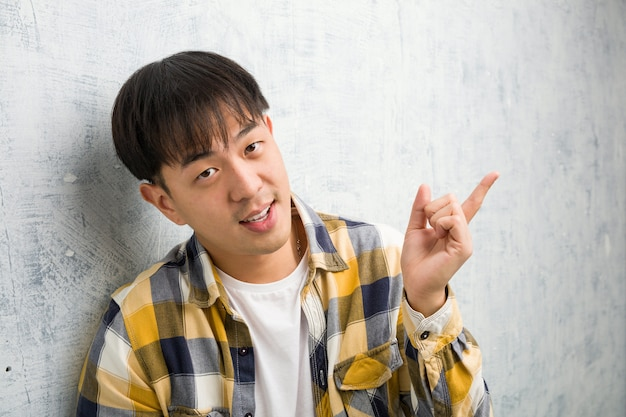 Young chinese man face closeup pointing to the side with finger