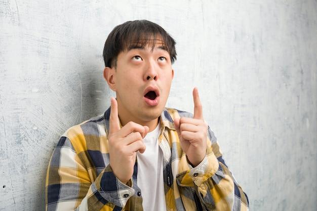 Молодой китайский человек лицо крупным планом удивлен, указывая вверх, чтобы показать что-то