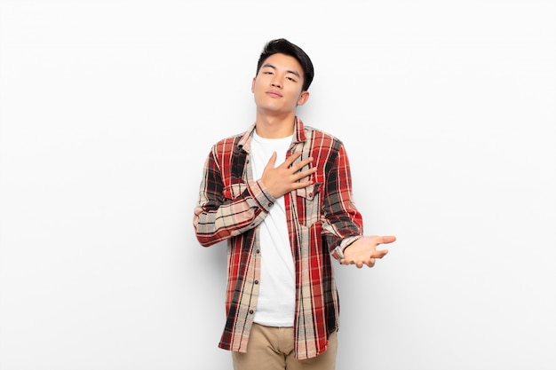 Young chinese man feeling happy and in love, smiling with one hand next to heart and the other stretched up front against flat color wall