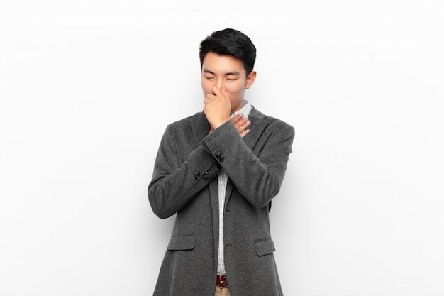 Молодой китаец чувствует себя плохо, с симптомами гриппа и болью в горле, кашляет, прикрыв ртом плоскую цветную стену