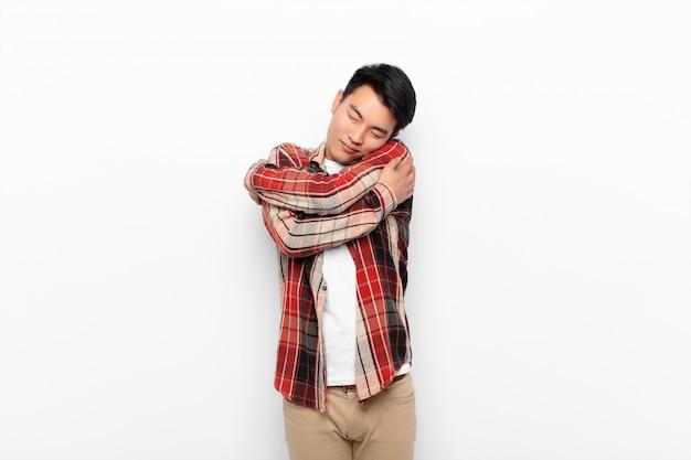 若い中国人男性の愛を感じ、笑顔、抱きしめ、抱きしめ、独身のままで、利己的でフラットカラーの壁に自己中心的