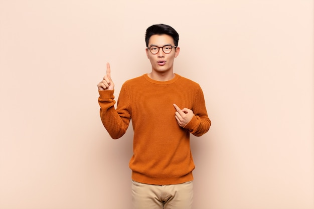Young chinese man feeling proud and surprised, pointing to self confidently, feeling like successful number one on flat color wall
