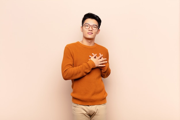 Young chinese man feeling romantic, happy and in love, smiling cheerfully and holding hands close to heart against flat color wall