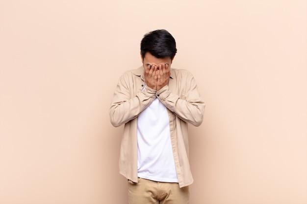 Молодой китаец грустит, расстроен, нервничает и подавлен, закрывает лицо обеими руками и плачет у плоской цветной стены