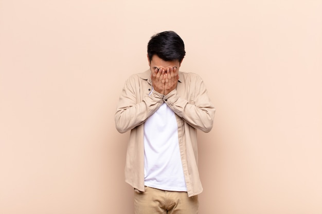 Young chinese man feeling sad, frustrated, nervous and depressed, covering face with both hands, crying against flat color wall