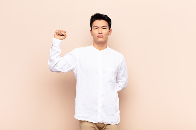 Young chinese man feeling serious, strong and rebellious, raising fist up, protesting or fighting for revolution against flat color wall