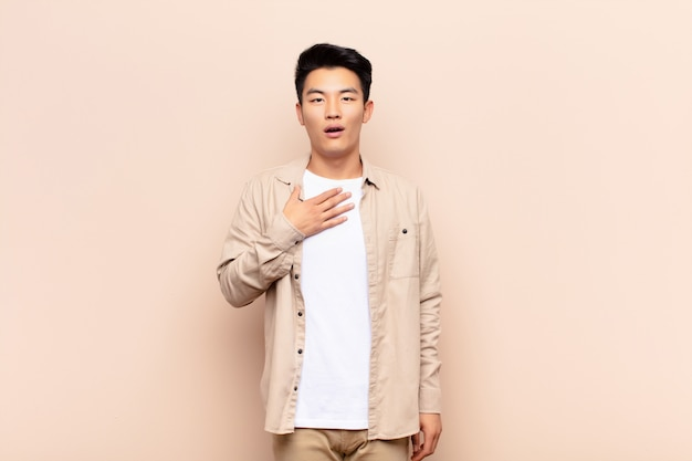 Young chinese man feeling shocked, astonished and surprised, with hand on chest and open mouth, saying who, me? on flat color wall