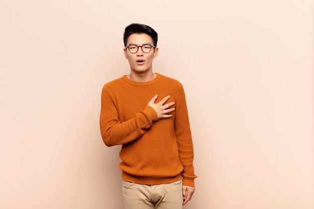 Young chinese man feeling shocked and surprised, smiling, taking hand to heart, happy to be the one or showing gratitude against flat color wall