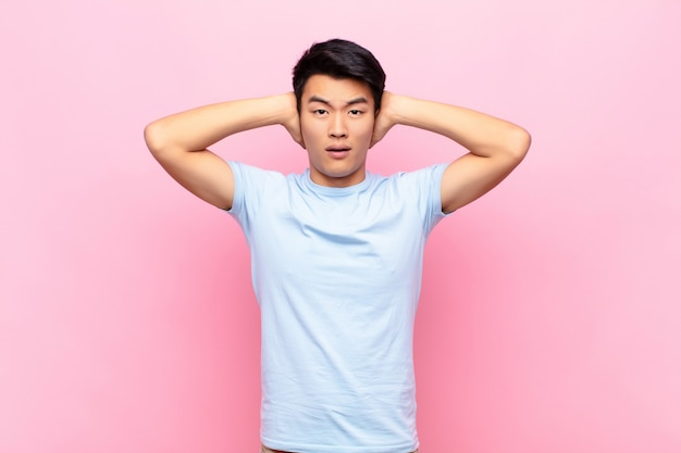 Young chinese man feeling stressed, worried, anxious or scared, with hands on head, panicking at mistake against flat color wall
