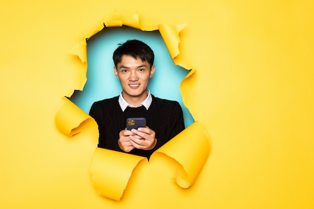 Young chinese man hold mobile phone keeps head in hole of torn yellow wall. male head in ripped paper.