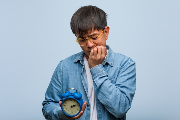 Young chinese man holding an alarm clock biting nails, nervous and very anxious