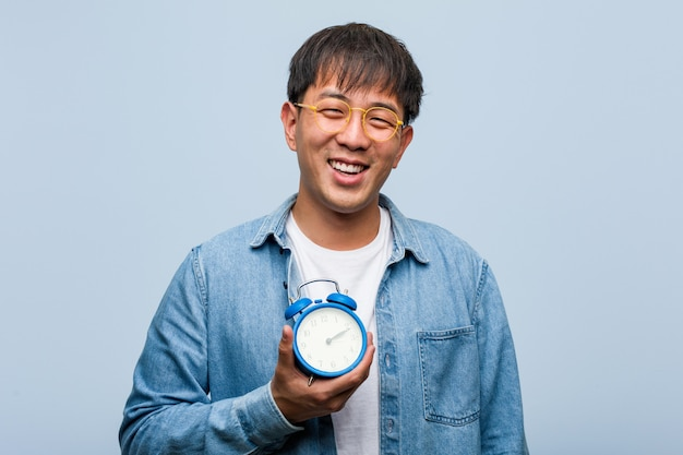 Young chinese man holding an alarm clock cheerful with a big smile