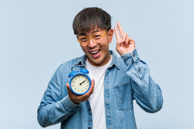 Young chinese man holding an alarm clock fun and happy doing a gesture of victory