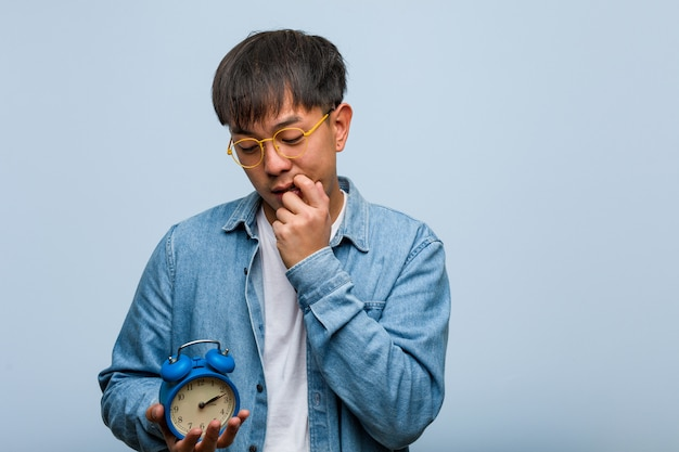 Young chinese man holding an alarm clock relaxed thinking about something looking at a copy space
