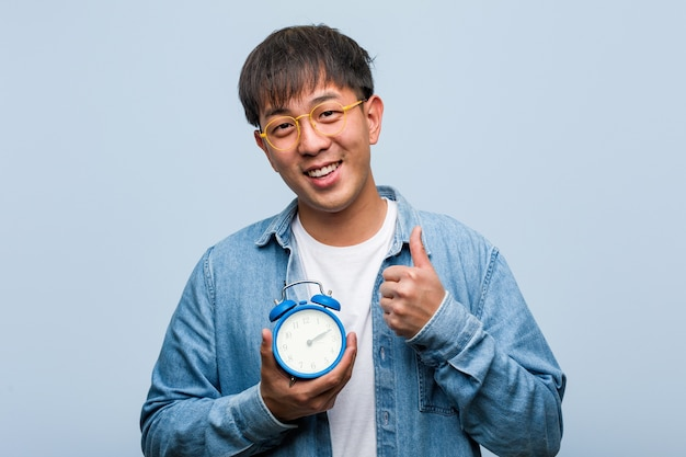 Young chinese man holding an alarm clock smiling and raising thumb up