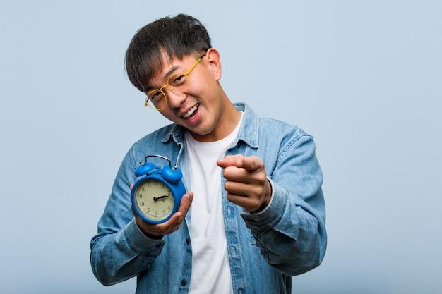目覚まし時計を持って陽気で笑顔の若い中国人男性