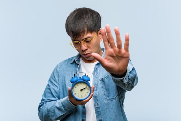 젊은 중국 남자 앞에 손을 넣어 알람 시계를 들고