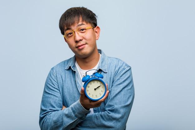 自信を持って笑顔で腕を組んで、見上げる目覚まし時計を保持している若い中国人男性
